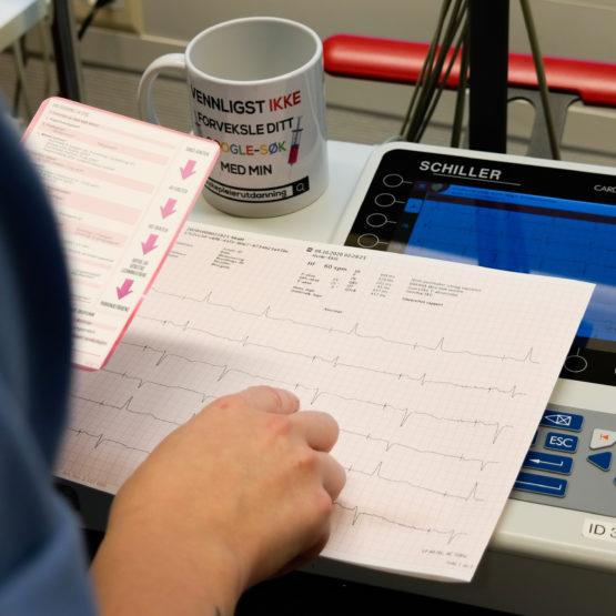 Bilde av helsepersonell på jobb med EKG-kort og kopp fra Cingulum AS
