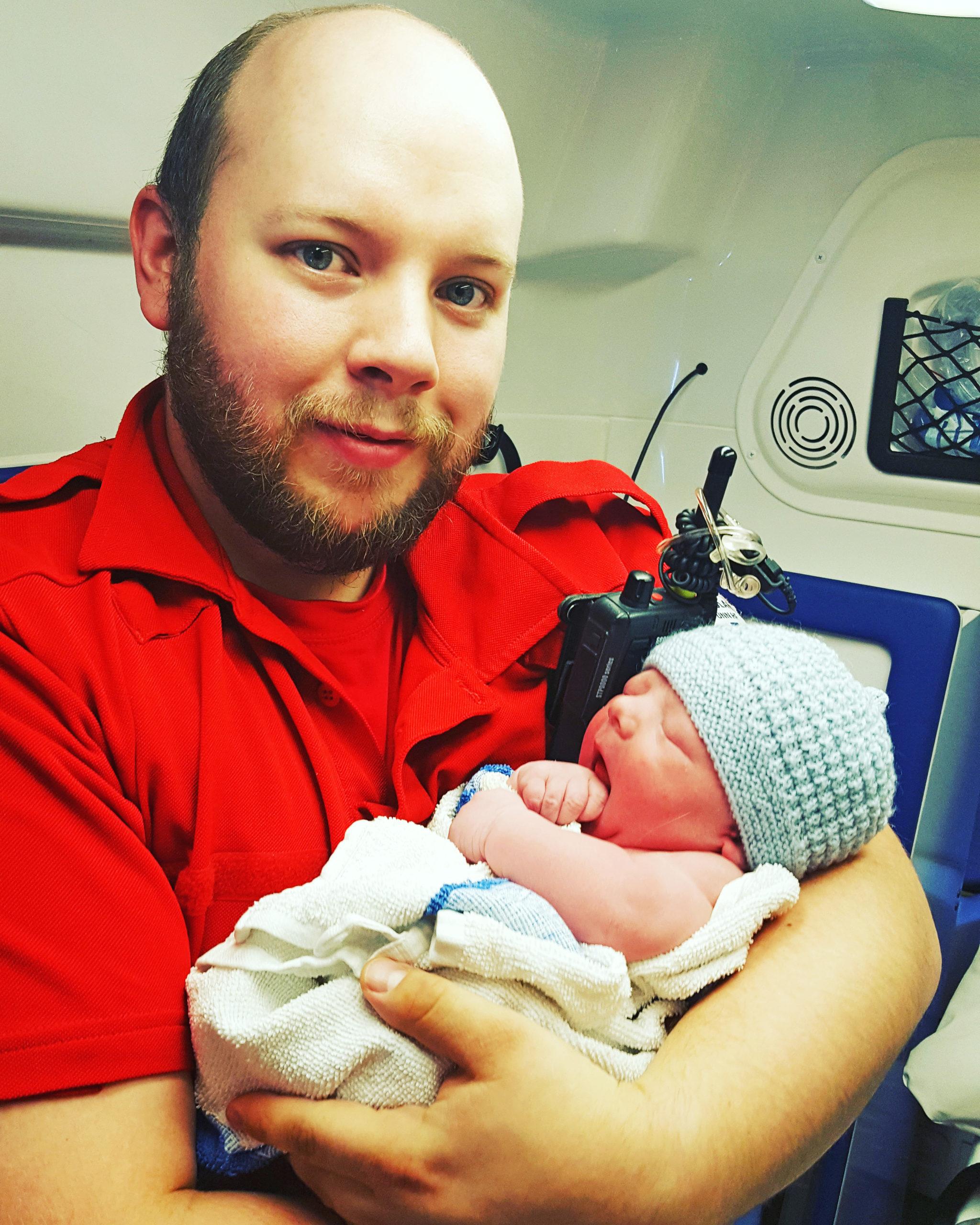Bilde av David Andersen som er ambulansearbeider, med nyfødt baby - Cingulum