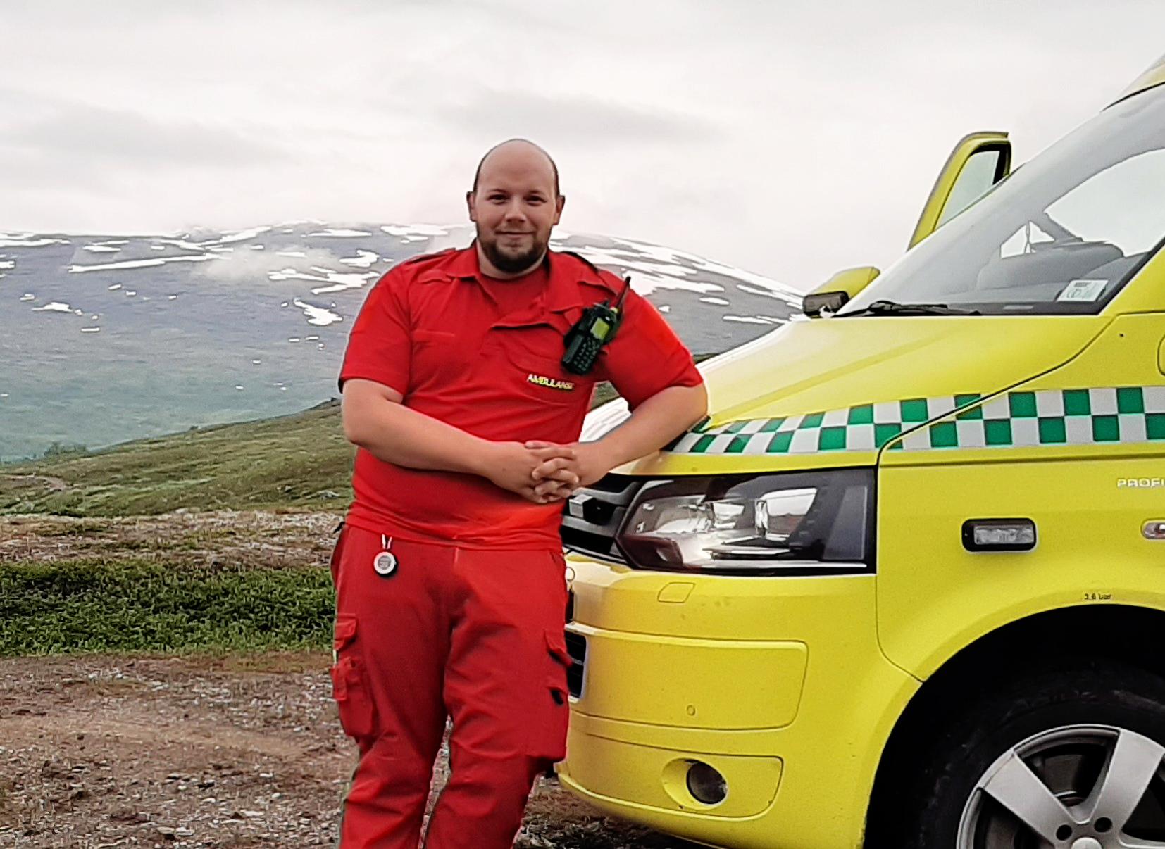 Bilde av David Andersen som er ambulansearbeider, foran ambulansen - Cingulum