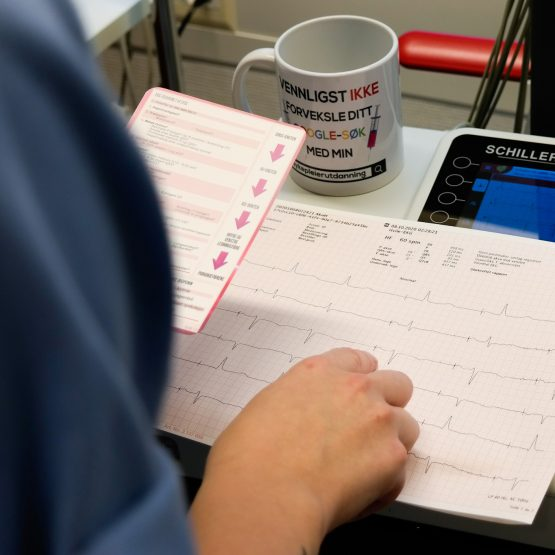 Bilde av helsepersonell med EKG medisinsk referansekort fra Cingulum